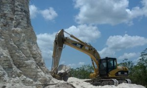 A digger claws away at the sloping sides of the Mayan pyramid in Belize
